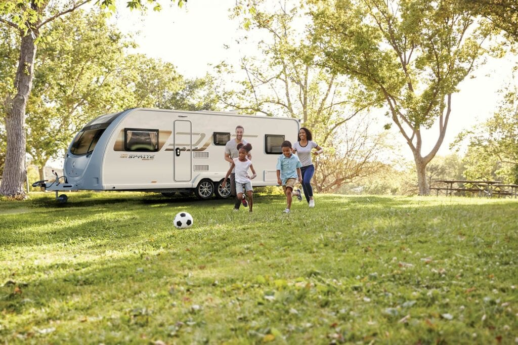 2021 Sprite Caravans: Image of a family playing football in front of a Sprite caravan.