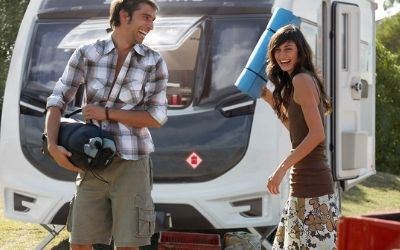 Help & Advice: Image of a young couple next to a caravan.