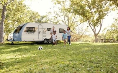 Help & Advice: Image of a young family in front of a caravan.